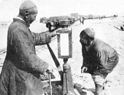 ASIATIC RAILWAY WORKERS examining the points on a stretch of track in Manchuria.