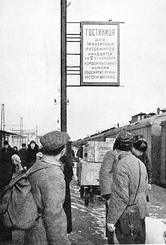 ARRIVAL IN MOSCOW. Travellers on a Moscow platform looking at a poster advertising a new railway hotel