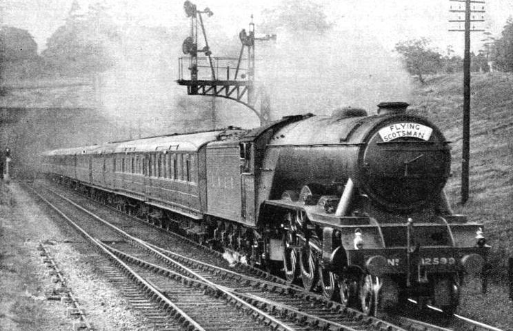"An impression of the ""Flying Scotsman"" - the LNER's most famous express - passing signals at speed near London"