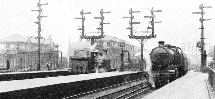 THE OLD AND THE NEW SYSTEMS. This view of Brighton station shows the semaphore-arm signals which were formerly in use. Compare it with the view below, which depicts the new colour-light signals that now control the same lines.